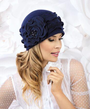 Caciula de dama Adel are un aer chic si romantic ce se datoreaza accesorizarii cu doua benzi late orizontale, tip volanase tricotate. In lateral se remarca floarea stilizata asemanatoare unui trandafir mare, inflort, ce are in mijloc un manunchi de margele