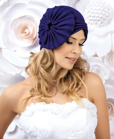 Caciula de dama stil turban Aja iese in evidenta prin modelul original si nonconformist. Rozeta stilizata aplicata in lateral si croiala in V pe frunte transforma aceasta caciula in vedeta accesoriilor pentru sezonul rece