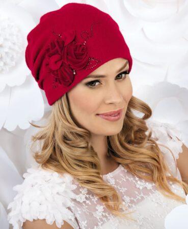 Caciula de dama eleganta Alondra se remarca prin ornamentul lateral sub forma unor trandafiri din catifea cu frunze din tricot. Aplicatia florala este completata cu strasuri ce ii sporesc farmecul si pliuri decorative la spate
