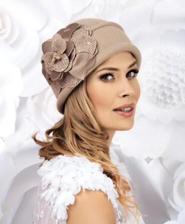 Caciula de dama eleganta Ana este un accesoriu ce nu poate trece neobservat. Decorul bogat, sub forma unei flori mari cu petale din tricot acoperit cu strasuri si satin, capteaza atentia de la prima privire