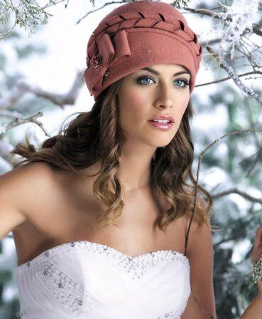 Caciula de dama eleganta Amina este spectaculoasa, bucurandu-se de o accesorizare aparte. Elementul de impact este reprezentat de bentita din panglici rasucite montata pe calota. In completarea acesteia vine si funda dubla din lateral ce are un manunchi de perle