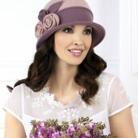 Caciula de dama stil palarie Henrietta este extrem de gratioasa si cucereste prin decorul floral cochet. In lateral are aplicati trei trandafiri stilizati din tricot in completarea carora vin cusaturile decorative ce urca pe calota