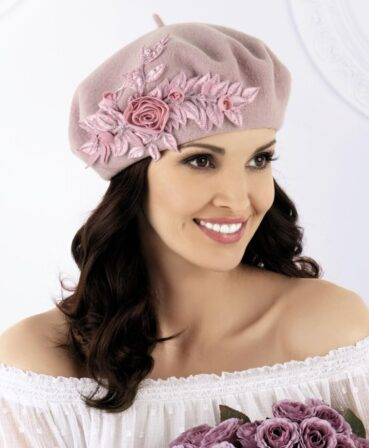 Caciula de dama stil bereta Macarena este o apartitie, atragand atentia de la prima privire. Nota eleganta este data de aplicatia florala bogata sub forma unor trandafiri cu frunzulite din material satinat ce au cusaturi decorative