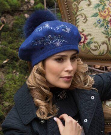 Caciula de dama stil bereta cu pompon din blanita Flitesa impresioneaza datorita accesorizarii deosebite cu strasuri dispuse sub forma unor crengute.