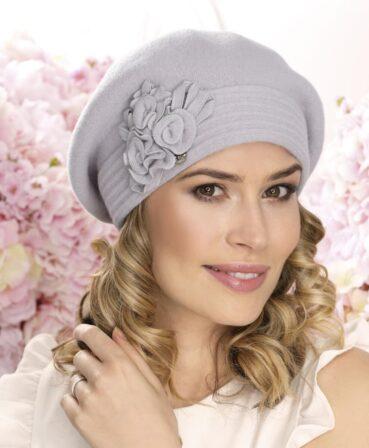 Caciula de dama tip bereta Tinita este un accesoriu cu accente romantice. Se remarca datorita marginii late din tricot dublu si a decorului floral discret.