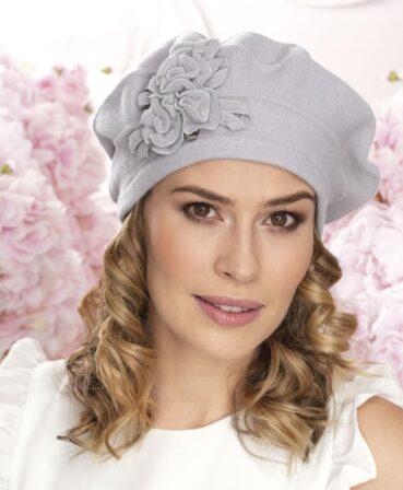 Caciula de dama tip bereta Tini este un accesoriu cu croiala clasica si detalii decorative discrete sub forma unor flori stilizate din tricot.